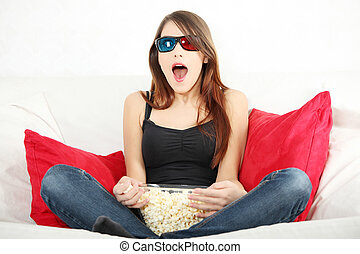 Beautiful young woman watching TV in 3d glasses and eating...