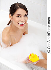 Woman taking a bath with yellow duck - Beautiful young...