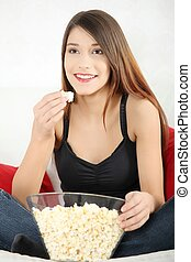 Popcorn - Beautiful young woman watching TV and eating...