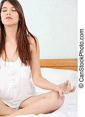 Woman on bed practicing yoga