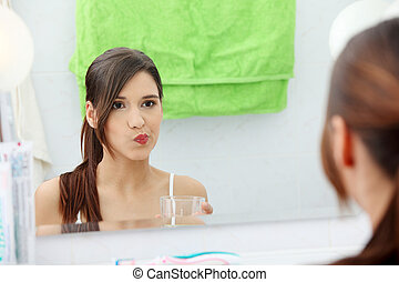 Woman using mouthwash - Young beautiful brunette woman using...