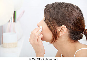 Young beautiful caucasian woman cleaning her face with...