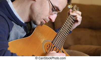 Guitar Picking - Man picks out a tune on an acoustic guitar.