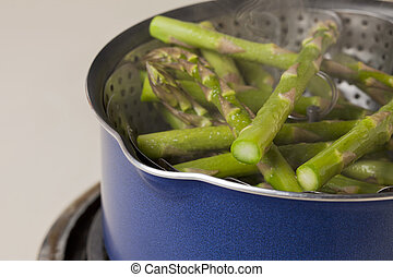 steaming green asparagus in a steamer basket inside blue pot