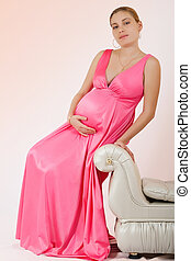 Portrait of a beautiful pregnant woman on a pink background