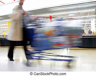 At the supermarket - Woman with cart in motion at the...