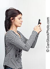 Young woman texting with cellphone - Pretty young brunette...