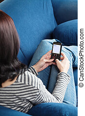 Woman sending SMS - Young brunette woman sitting on blue...