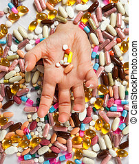 Drowning in pills - Female hand drowning in an ocean of...