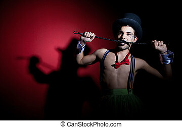 Performer in top hat with whip - Performer in top hat biting...