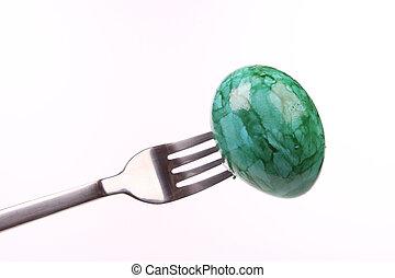 Easteregg on a fork - eateregg on a fork isolated over white...