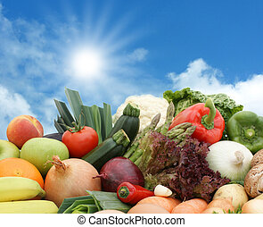 Fruit and vegetables against a sunny sky - A mixture of...