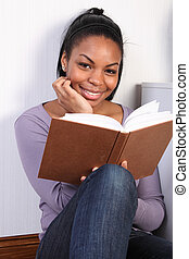 Beautiful happy african girl reading a book - Portrait of...