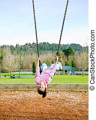 Happy little nine year old part Asian girl swinging upside...