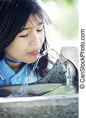 Girl drinking from fountain - Girl drinking from water...