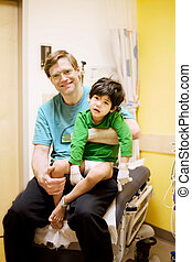 Father holding his sick disabled son in doctors office