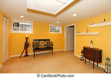Yellow basement design with black bench