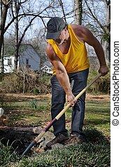 Digger - landscaper digging a pond.