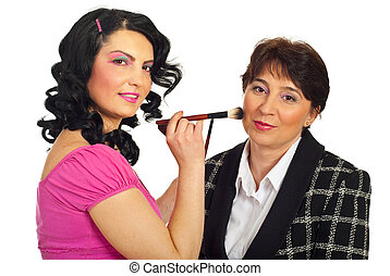 Beautician applying brush to model - Beautician woman with...