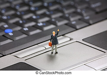 Businessman needs help with laptop - Miniature businessman...