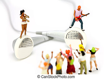 Miniature singer and guitar player standing on a pair of ear buds