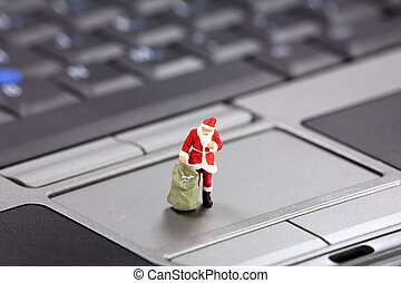 Christmas shopping online concept - Miniature Santa Claus...