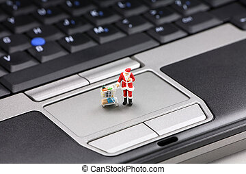 Online Christmas shopping concept. Miniature Santa Claus...