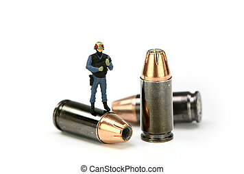 Miniature police officer in SWAT gear standing on a bullet