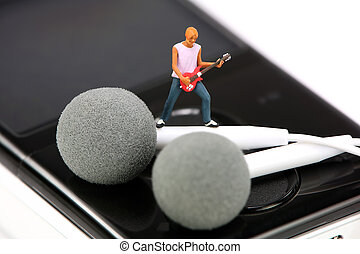 Miniature guitar player standing on a pair of ear buds
