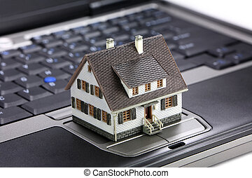 Online real estate concept - Miniature model home sitting on...