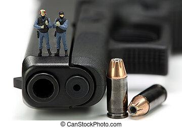 Miniature SWAT team standing on a gun