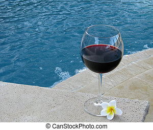"""Set for a """"staycation"""" with wine and plumeria petals in the backyard pool and suana."""