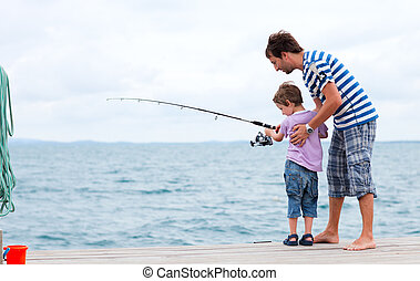 Father and son fishing together - Young father and his son...