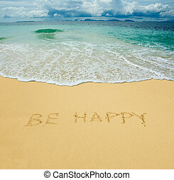 be happy written in a sandy tropical beach