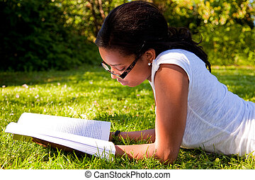 Young Student reading books at the school park - Young...