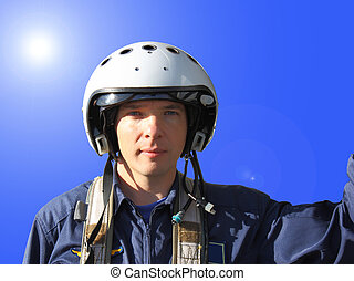 The military pilot in a helmet in dark blue overalls...