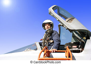 The military pilot in the plane in a helmet in dark blue...