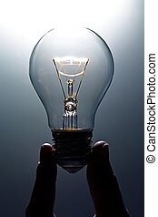Lit light bulb - A magically lit light bulb with two finger...