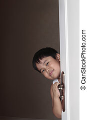 Boy peeping out from behind door