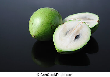 Sliced Starapple - Two pieces starapple, one sliced, placed...