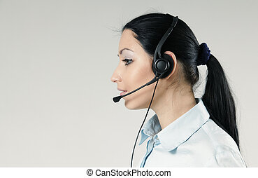 Attractive call center operator portrait. Sexy girl wearing headset standing on uniform background. One of a series.