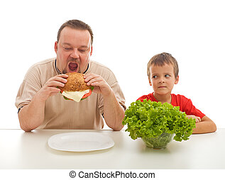 Healthy eating - teaching by example - Man eating hamburger...