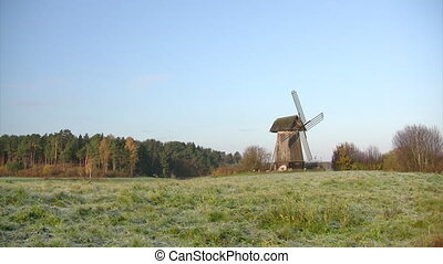 Old windmill - Old wooden mill on autumn forest background...