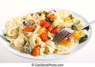 Tagliatelle and tomatoes with fork - A plate of tagliatelli...