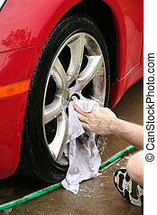 A man washing a wheel of a car. There is slight motion blur...
