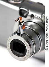 Miniature photographer standing on a camera lens - A...