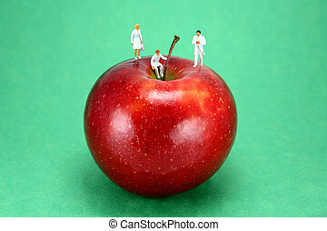 Miniature doctors standing on an apple
