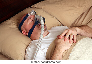 Man with sleep apnea using a CPAP machine - Caucasian man...
