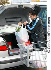 woman putting groceries in trunk - young woman putting a bag...