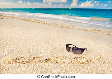 Black sun glasses on white sand beach and word vocation near...
